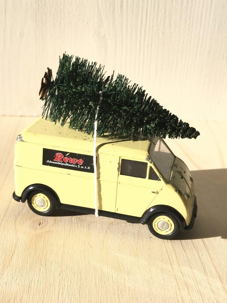 Spielzeugauto mit Tannenbaum auf dem Dach