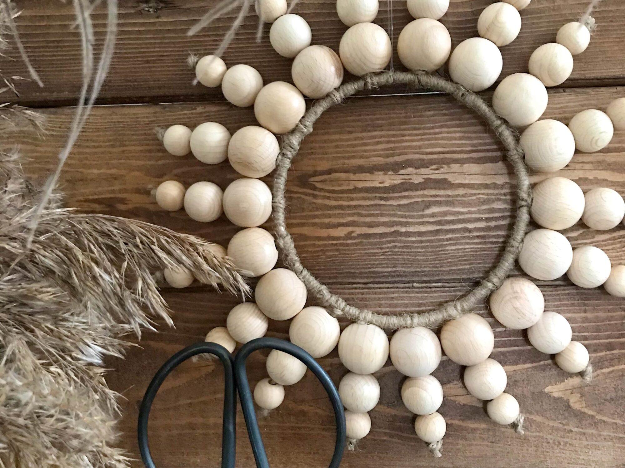 DIY Holzperlen Kranz als Wanddeko. Basteln mit Holzperlen. #chalet8 #holzperlen #holzkugeln #holzperlenkranz #holzkugelkranz